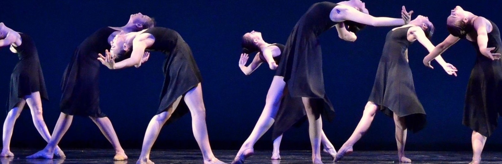 Dance Cavise dancers on stage in black dresses performing a modern dance at a performance at SUNY Purchase